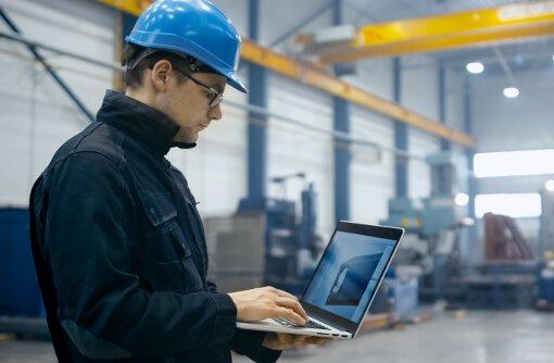 facility manager nutzt laptop für das industriemanagement