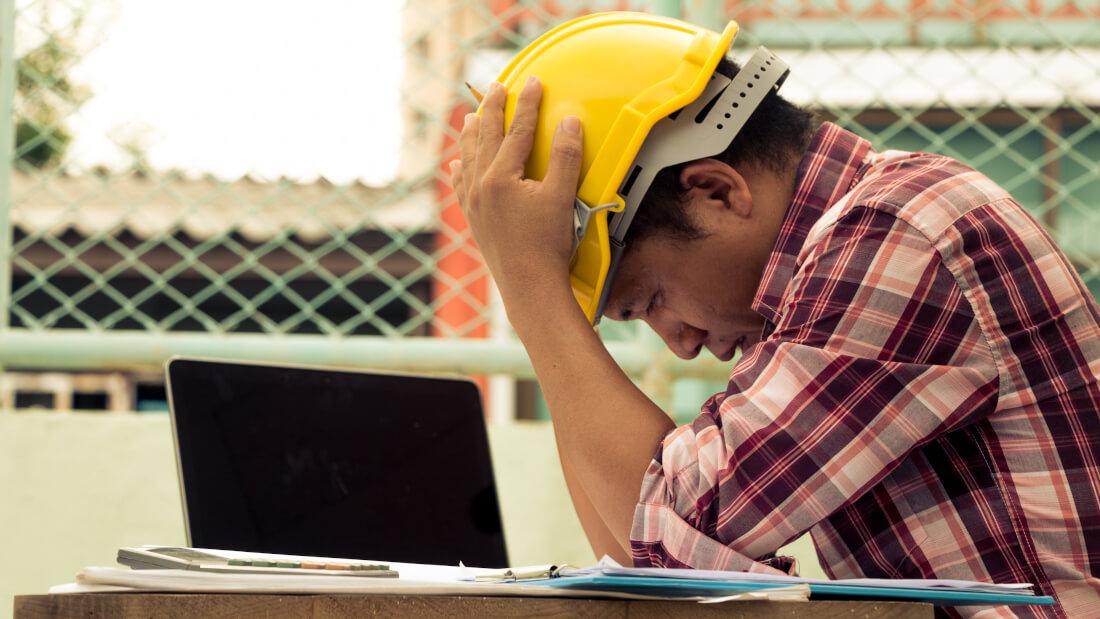 Bauarbeiter sitzt verzweifelt am Tisch