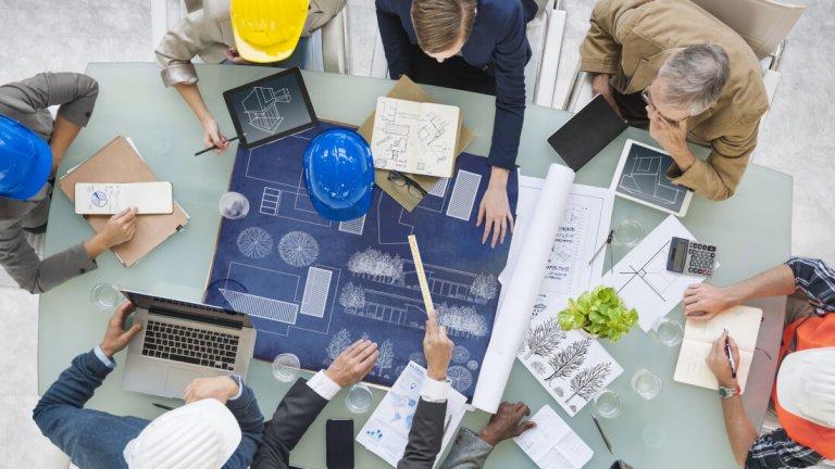 Arbeiter besprechen einen Entwurf an einem Tisch